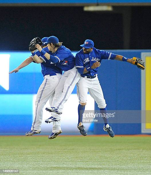 Travis Snider, Colby Rasmus and Rajai Davis of the Toronto Blue Jays celebrate the teams win over the Oakland Athletics during MLB game action July...