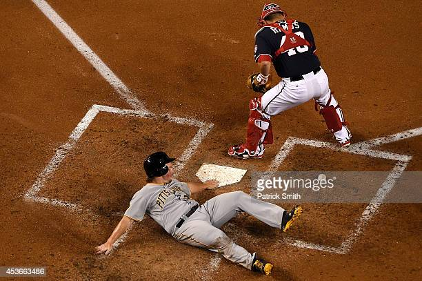 Travis Snider of the Pittsburgh Pirates scores as catcher Wilson Ramos of the Washington Nationals cannot handle the throw in the fourth inning at...