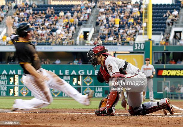 Travis Snider of the Pittsburgh Pirates slides in safe against Miguel Montero of the Arizona Diamondbacks in the third inning during the game on...