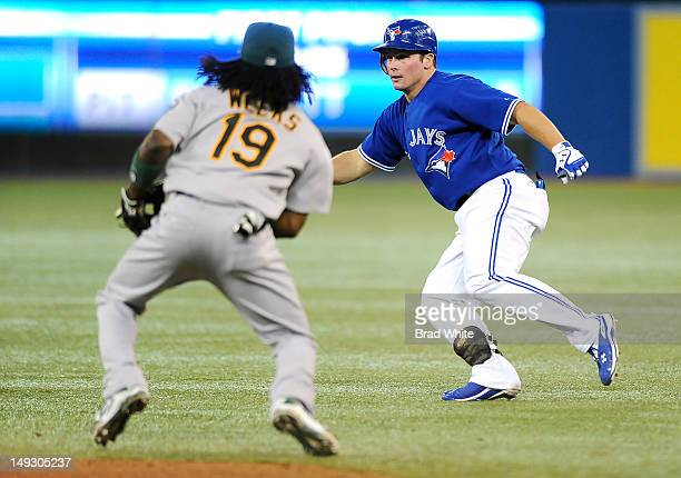 Travis Snider of the Toronto Blue Jays gets caught in a run down by Jemile Weeks of the Oakland Athletics during MLB game action July 26, 2012 at...
