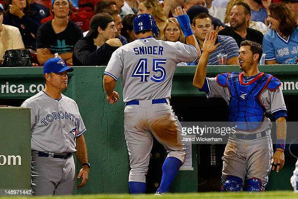Travis Snider of the Toronto Blue Jays is congratulated in the dugout by teammate J.P. Arencibia after scoring in the 9th inning against the Boston...