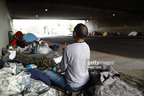 Travis Stanley who said he has been homeless for three months and is a US Navy veteran sits on donated bedding where he normally sleeps beneath an...