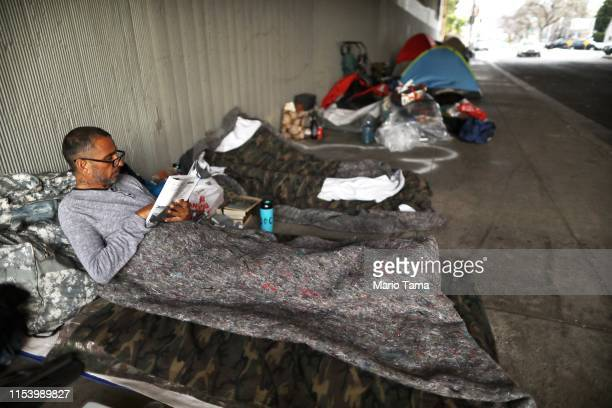 Travis Stanley who said he has been homeless for three months and is a US Navy veteran reads on donated bedding where he normally sleeps beneath an...