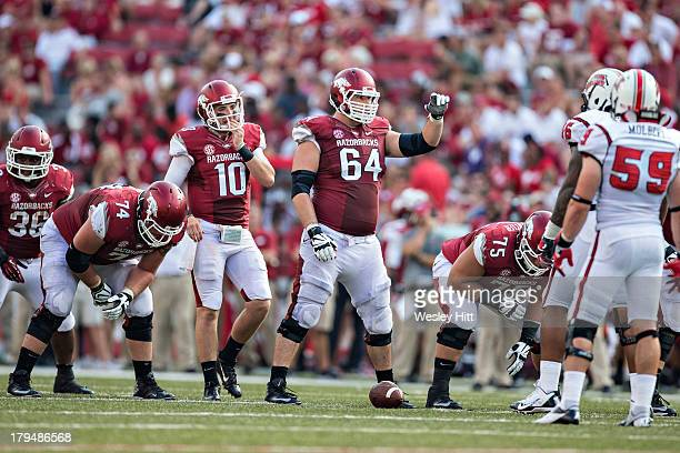 Travis Swanson of the Arkansas Razorbacks signals at the line of scrimmage during a game against the Louisiana-Lafayette Ragin Cajuns at Razorback...