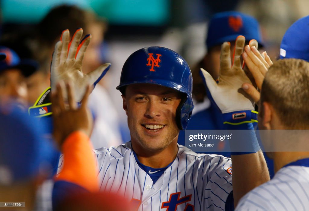 Travis Taijeron #28 of the New York Mets celebrates his second inning home run against the Cincinnati Reds in the dugout with his teammates at Citi Field on September 8, 2017 in the Flushing neighborhood of the Queens borough of New York City. The home run was the first in the major leagues for Taijeron.