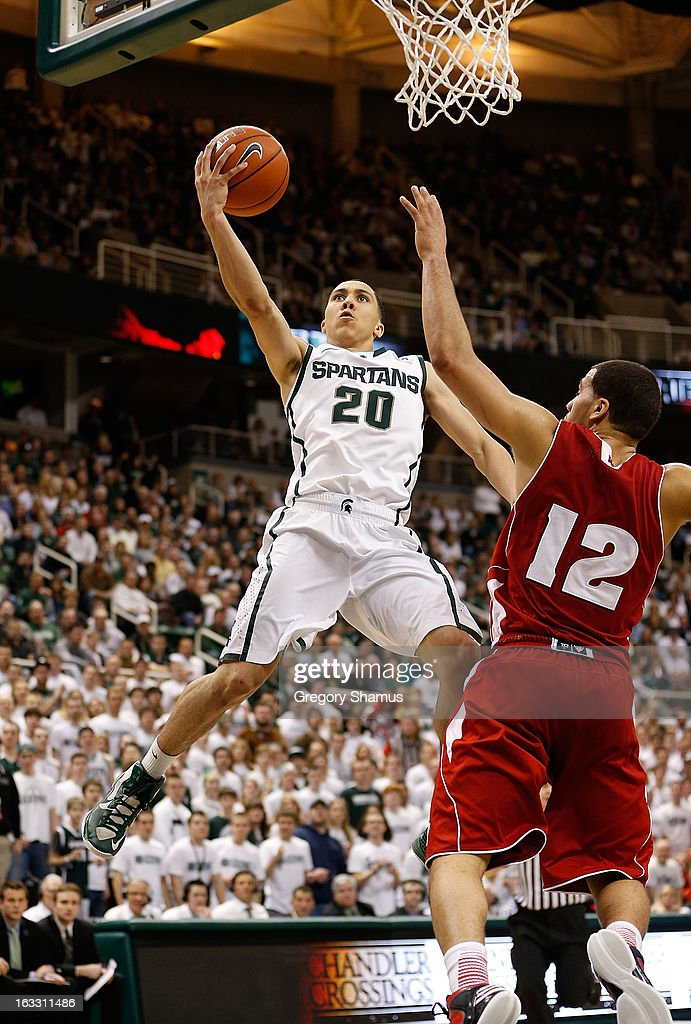 Travis Trice #20 of the Michigan State Spartans gets to the basket in the second half next to Traevon Jackson #12 of the Wisconsin Badgers at the Jack T. Breslin Student Events Center on March 7, 2013 in East Lansing, Michigan. Michigan State won the game 58-43.