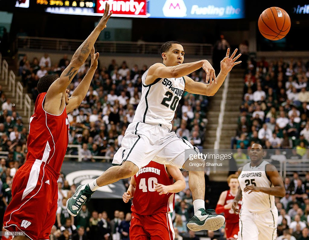 Travis Trice #20 of the Michigan State Spartans passes out of the paint in front of George Marshall #3 of the Wisconsin Badgers at the Jack T. Breslin Student Events Center on March 7, 2013 in East Lansing, Michigan. Michigan State won the game 58-43.