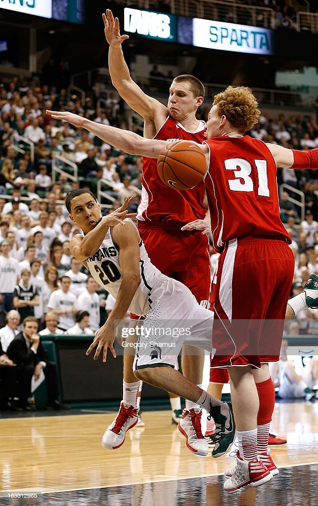 Travis Trice #20 of the Michigan State Spartans passes while cutting between Mike Bruesewitz #31 and Jared Berggren #40 of the Wisconsin Badgers during the second half at the Jack T. Breslin Student Events Center on March 7, 2013 in East Lansing, Michigan.