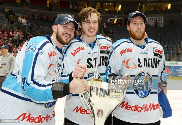 Travis Turnbull , Ziga Jeglic and Robert Sabolic hold after game seven of the DEL playoff final on April 29, 2014 in Cologne, Germany.