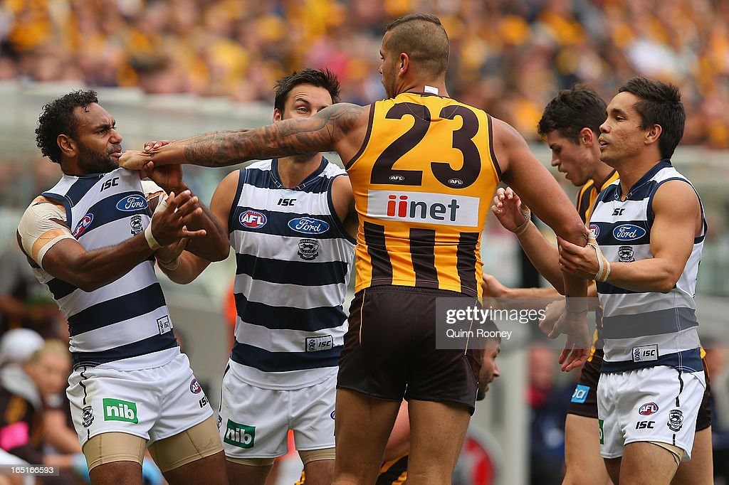 Travis Varcoe of the Cats and Lance Franklin of the Hawks wrestle during the round one AFL match between the Hawthorn Hawks and the Geelong Cats at the Melbourne Cricket Ground on April 1, 2013 in Melbourne, Australia.