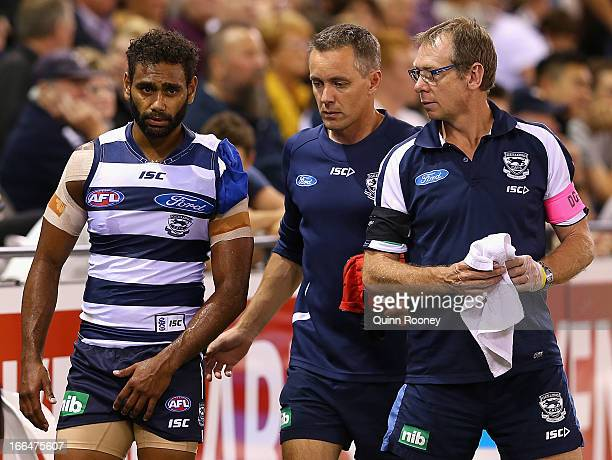 Travis Varcoe of the Cats walks around the boundary line with an injured shoulder during the round three AFL match between the Geelong Cats and the...