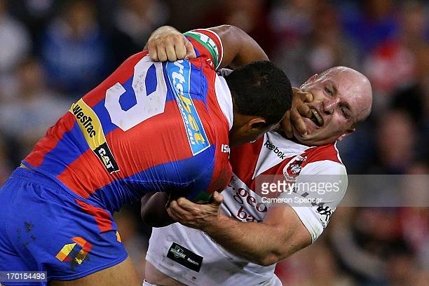 Travis Waddell of the Knights is tackled by Michael Weyman of the Dragons during the round 13 NRL match between the Newcastle Knights and the St...