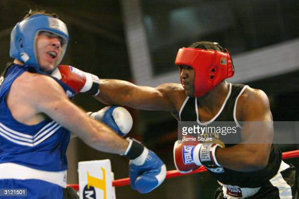 Travis Walker lands a punch on the chin of Nicolai Firtha during their bout in the United States Olympic Team Boxing Trials at Tunica Arena and...