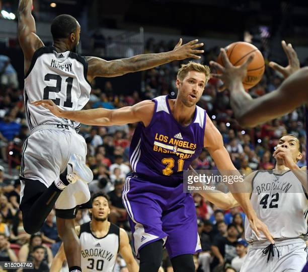 Travis Wear of the Los Angeles Lakers passes the ball under the basket against Kamari Murphy of the Brooklyn Nets during the 2017 Summer League at...