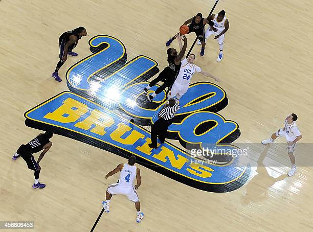 Travis Wear of the UCLA Bruins and Demondre Chapman of the Prairie View AM Panthers jump for the opening tipoff at Pauley Pavilion on December 14...