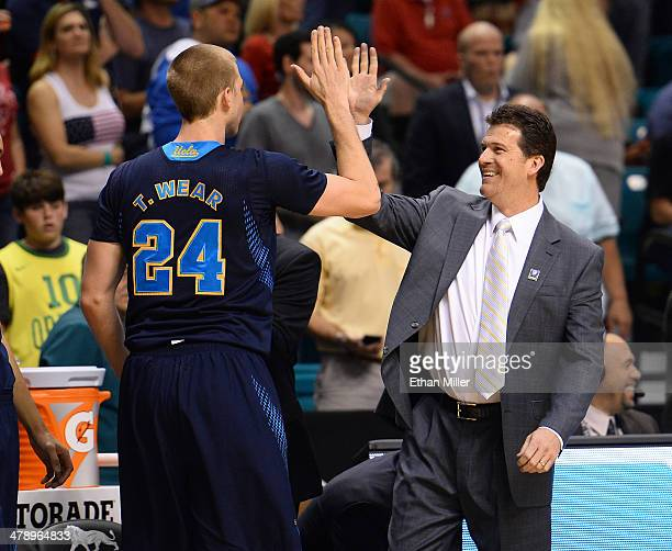Travis Wear of the UCLA Bruins high fives head coach Steve Alford after they took the lead against the Arizona Wildcats during the championship game...