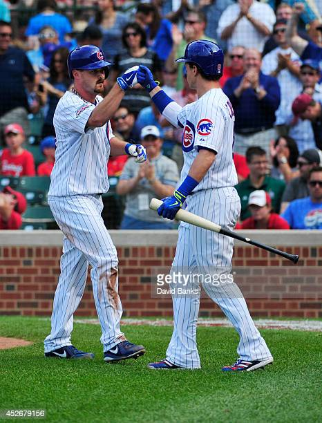 Travis Wood of the Chicago Cubs is greeted by Chris Coghlan of the Chicago Cubs after hitting a home run against the St Louis Cardinals during the...