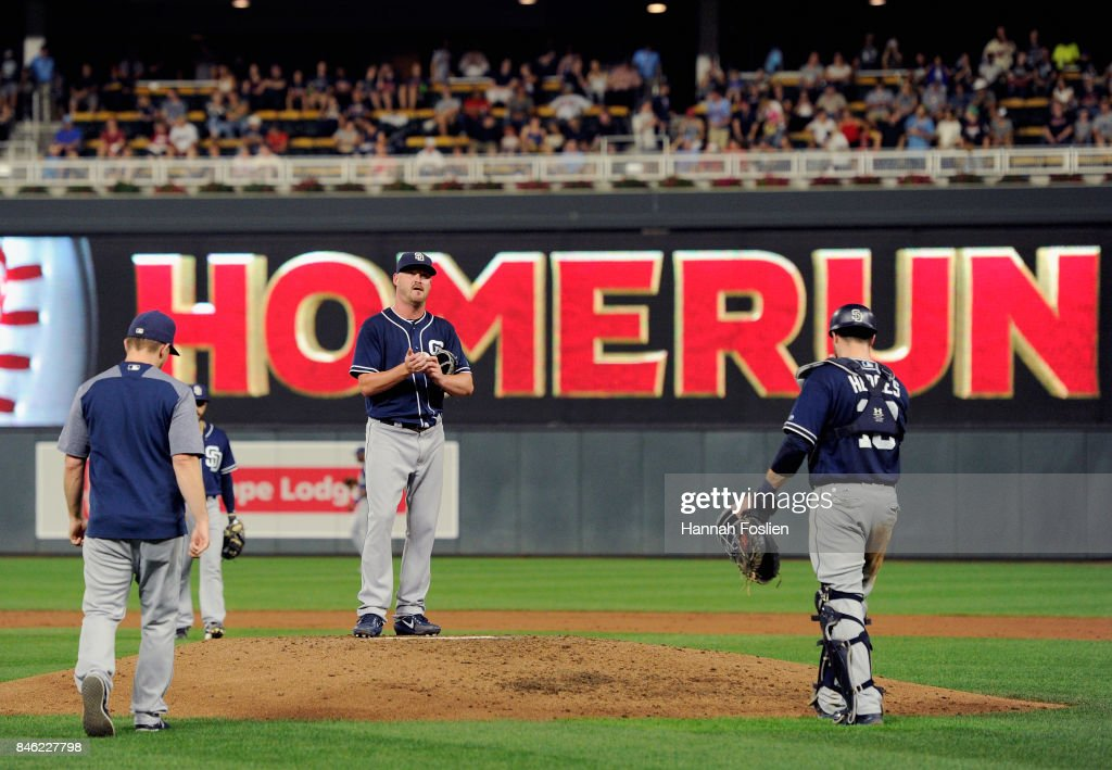 Travis Wood #37 of the San Diego Padres reacts as manager Andy Green #14 and catcher Austin Hedges #18 head to the mound to relieve him from the game against the Minnesota Twins during the third inning on September 12, 2017 at Target Field in Minneapolis, Minnesota.