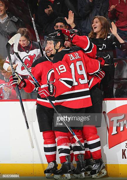 Travis Zajac and Kyle Palmieri congratulate John Moore of the New Jersey Devils after Moore scored the game winning goal in overtime against the...