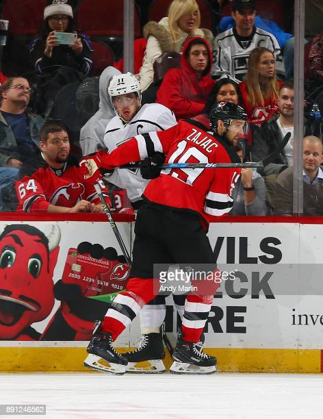 Travis Zajac of the New Jersey Devils and Anze Kopitar of the Los Angeles Kings come together at the boards during the game at Prudential Center on...