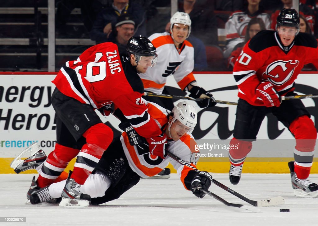 Travis Zajac #19 of the New Jersey Devils and Danny Briere #48 of the Philadelphia Flyers battle for the puck at the Prudential Center on March 13, 2013 in Newark, New Jersey.