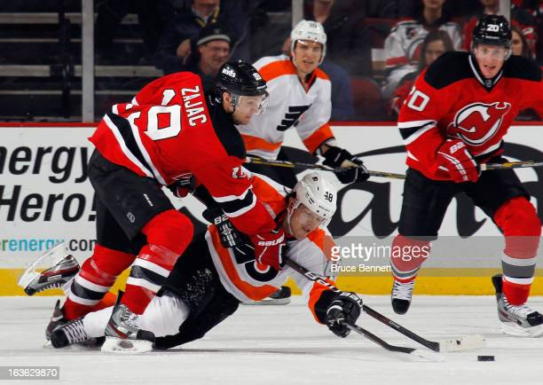 Travis Zajac of the New Jersey Devils and Danny Briere of the Philadelphia Flyers battle for the puck at the Prudential Center on March 13 2013 in...