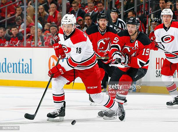 Travis Zajac of the New Jersey Devils and Jay McClement of the Carolina Hurricanes battle for position during the game at the Prudential Center on...