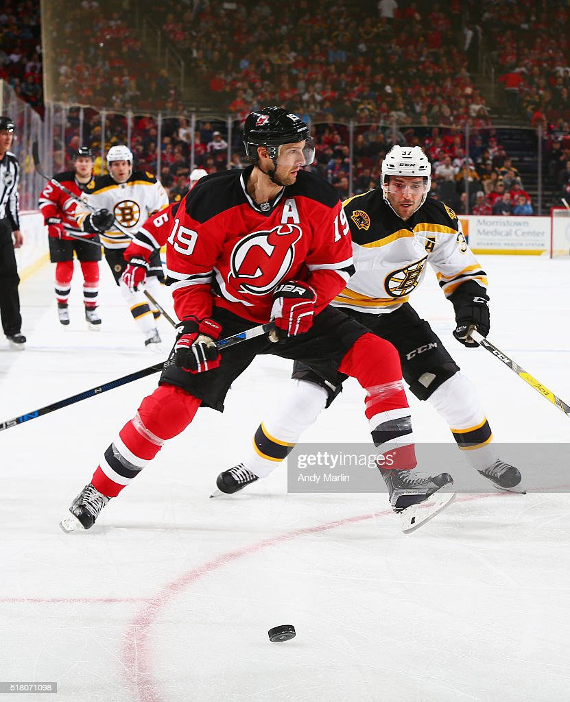 Travis Zajac #19 of the New Jersey Devils and Patrice Bergeron #37 of the Boston Bruins pursue a loose puck during the game at the Prudential Center on March 29, 2016 in Newark, New Jersey.