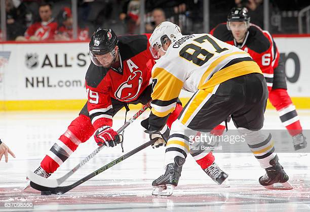 Travis Zajac of the New Jersey Devils and Sidney Crosby of the Pittsburgh Penguins face off an NHL hockey game at Prudential Center on December 27...