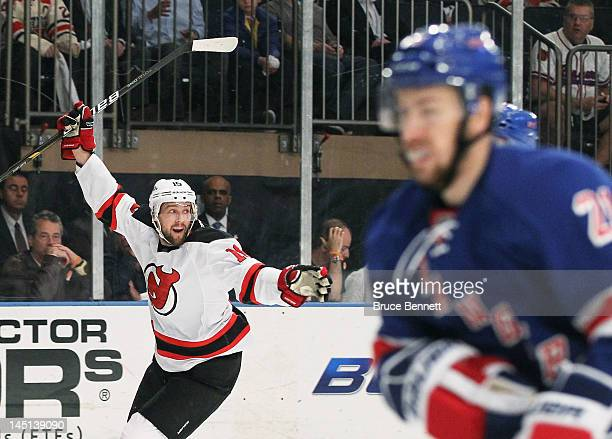 Travis Zajac of the New Jersey Devils celebrates his first period goal as Ryan Callahan of the New York Rangers reacts in Game Five of the Eastern...