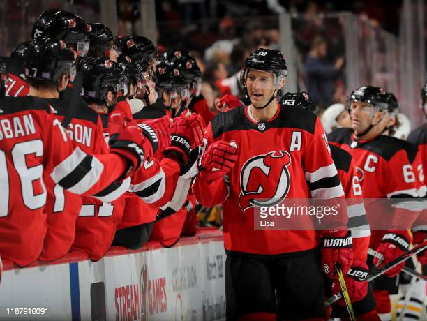 Travis Zajac of the New Jersey Devils celebrates his goal with teammates on the bench in the first period against the Pittsburgh Penguins at...