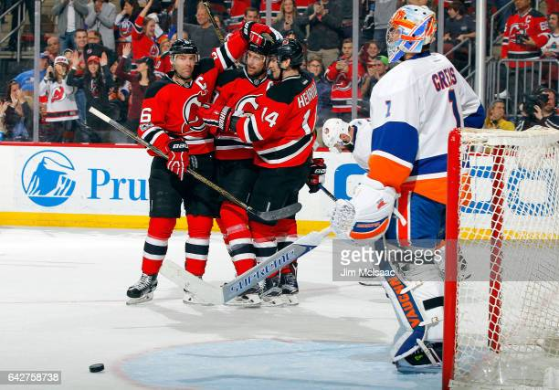 Travis Zajac of the New Jersey Devils celebrates his second period short handed goal against Thomas Greiss of the New York Islanders with teammates...