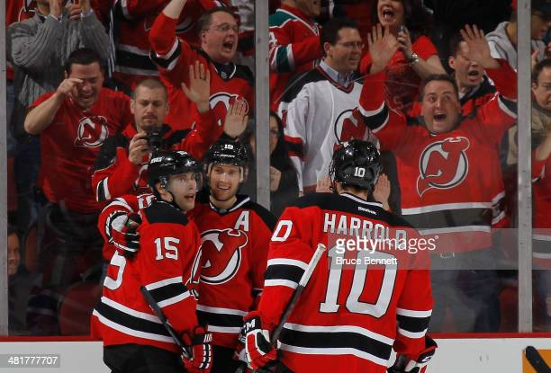 Travis Zajac of the New Jersey Devils celebrates his third goal of the game against the Florida Panthers along with Tuomo Ruutu and Peter Harrold at...