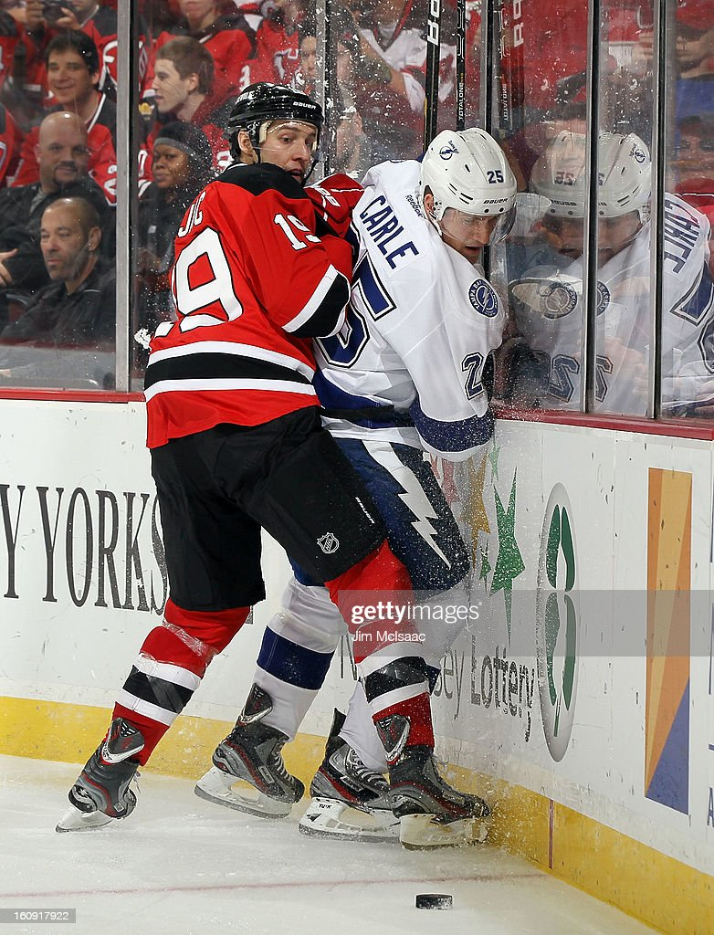 Travis Zajac #19 of the New Jersey Devils checks Matt Carle #25 of the Tampa Bay Lightning at the Prudential Center on February 7, 2013 in Newark, New Jersey.