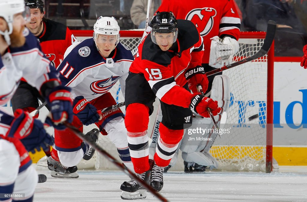 Travis Zajac #19 of the New Jersey Devils clears the puck from Matt Calvert #11 of the Columbus Blue Jackets during the second period on February 20, 2018 at Prudential Center in Newark, New Jersey.