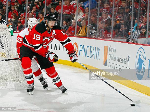 Travis Zajac of the New Jersey Devils controls the puck away from Mike Green  of the 25c4aae92
