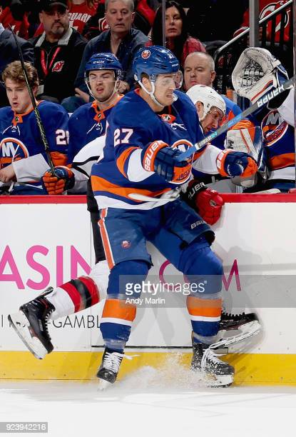 Travis Zajac of the New Jersey Devils is checked into the boards by Anders Lee of the New York Islanders during the game at Prudential Center on...