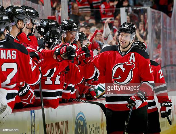 Travis Zajac of the New Jersey Devils is congratulated by teammates on the bench after he scored an empty net goal in the third period against the...