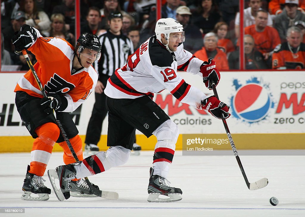 Travis Zajac #19 of the New Jersey Devils passes the puck while being pursued by Brayden Schenn #10 of the Philadelphia Flyers on March 15, 2013 at the Wells Fargo Center in Philadelphia, Pennsylvania.