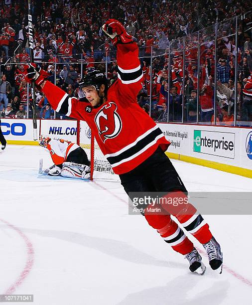 Travis Zajac of the New Jersey Devils raises his arms in celebration of his game deciding goal in a shootout against the philadelphia Flyers at the...