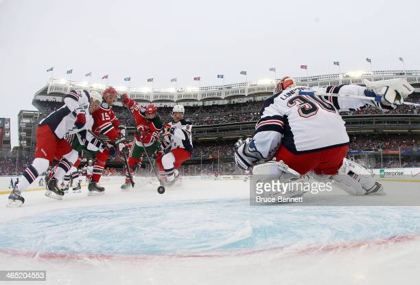 Travis Zajac of the New Jersey Devils score a first period goal against Henrik Lundqvist of the New York Rangers during the 2014 Coors Light NHL...