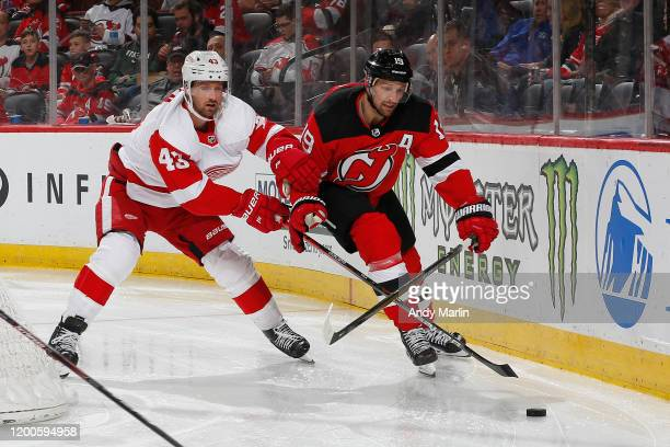 Travis Zajac of the New Jersey Devils skates for the puck against Darren Helm of the Detroit Red Wings during the game at the Prudential Center on...