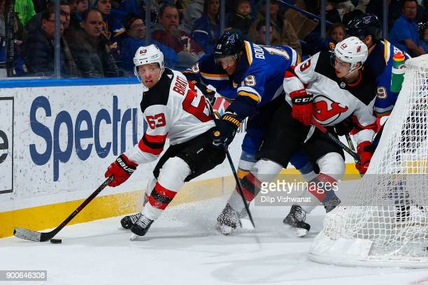 Travis Zajac of the St Louis Blues defends against Jesper Bratt and Nico Hischier of the New Jersey Devils at Scottrade Center on January 2 2018 in...