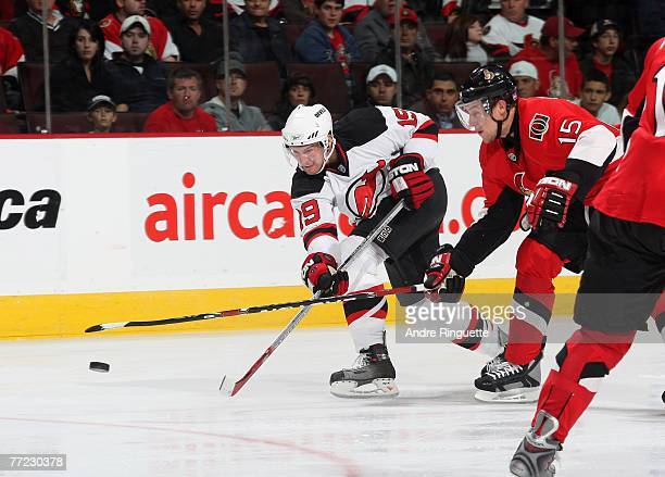 Travis Zajac the New Jersey Devils fights off Dany Heatley of the Ottawa Senators for a clear shot on net at Scotiabank Place on October 8, 2007 in...
