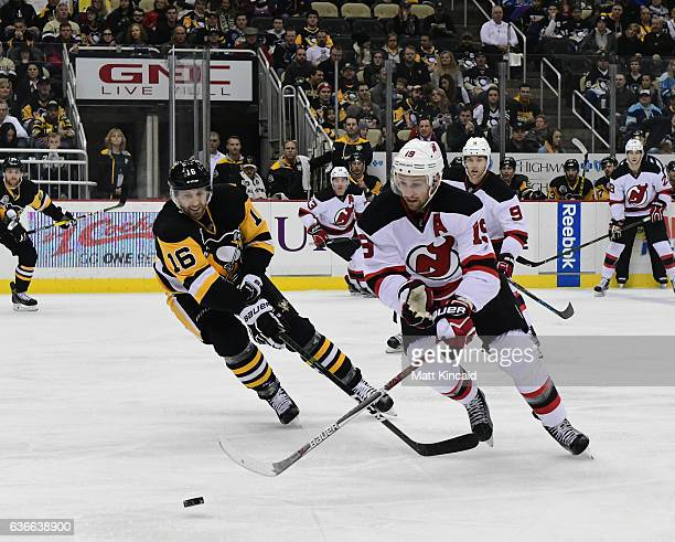Travis Zajec of the New Jersey Devils reaches for the puck against Eric Fehr the Pittsburgh Penguins at PPG PAINTS Arena on December 23 2016 in...