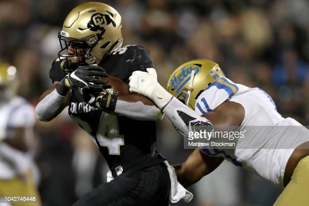 Travon McMillian of the Colorado Buffaloes carries the ball against Keisean LucierSouth of the UCLA Bruins in the second quarter at Folsom Field on...