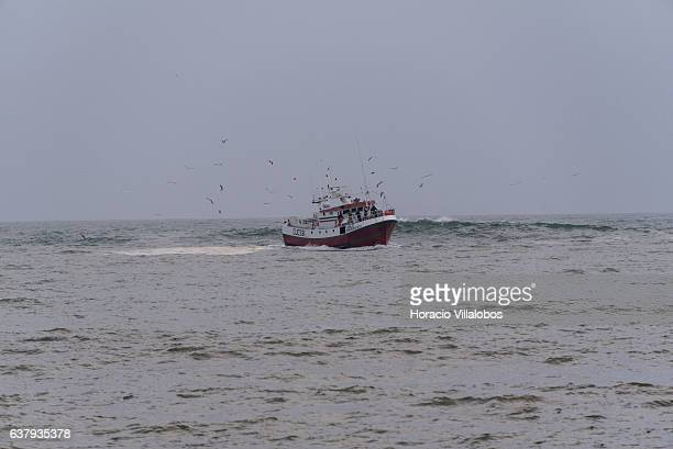 A trawler is seen entering harbor from Praia da Duquesa in stormy weather on January 03 2017 in Cascais Portugal