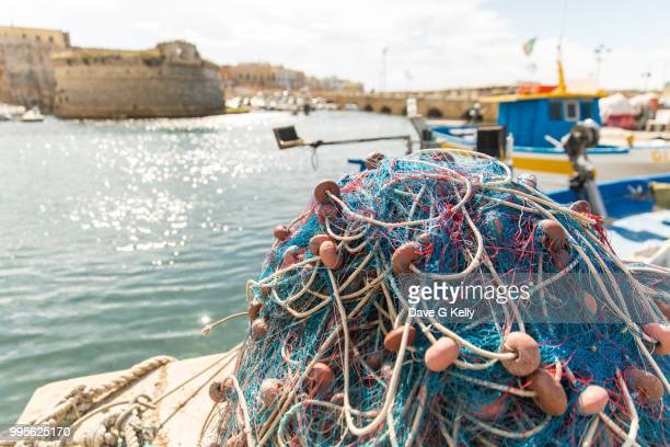 Trawler Net in a Mound on a Pier with Castle in Background