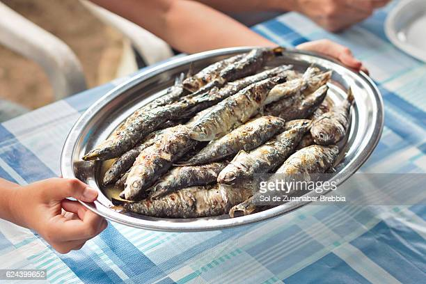 Tray full of freshly roasted sardines about to be served