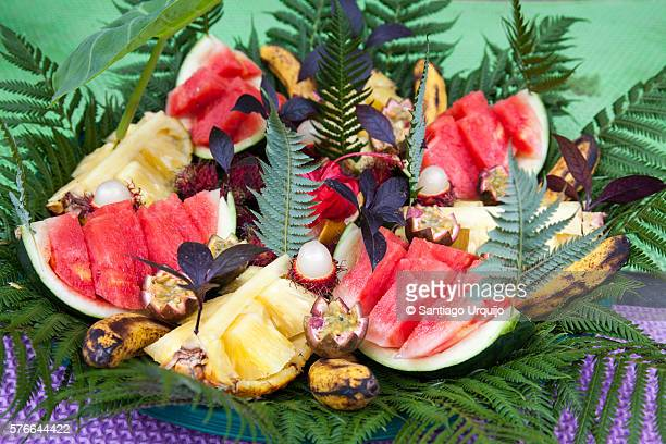 tray of fruit adorned with ferns - tropische frucht stock-fotos und bilder